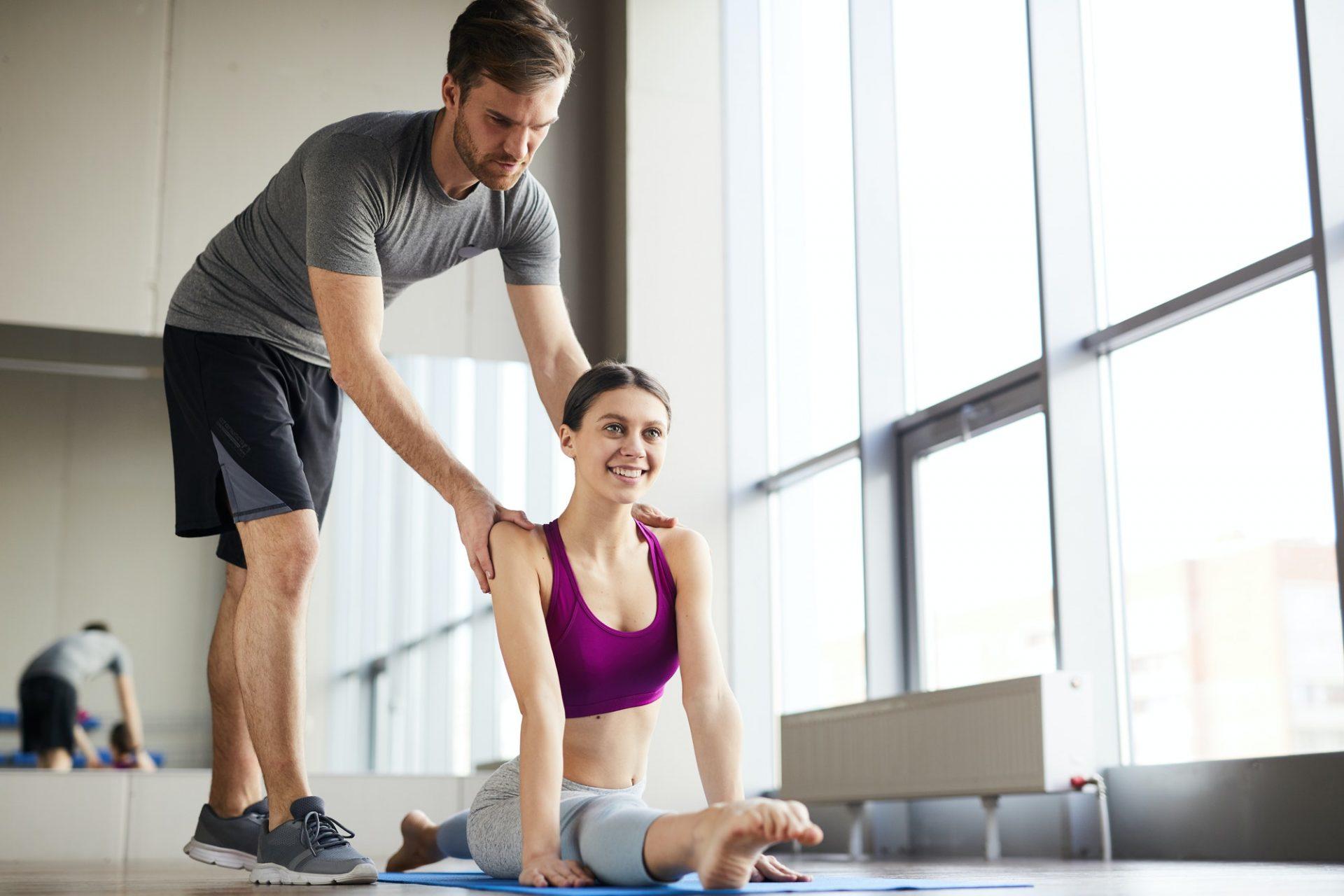 Male pilates coach adjusting back of flexible girl