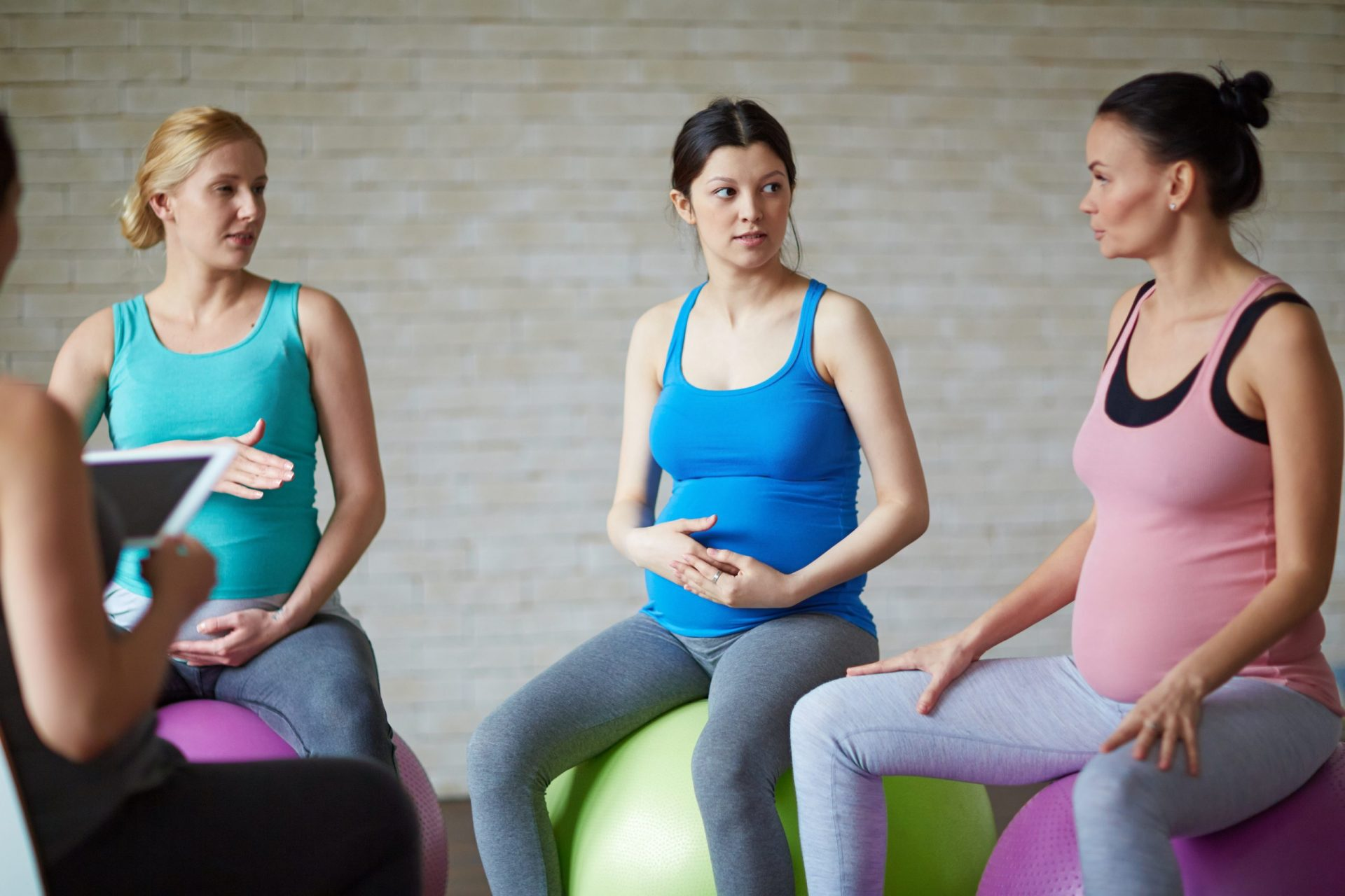 Active pregnant women sitting on fit-balls in gym and talking